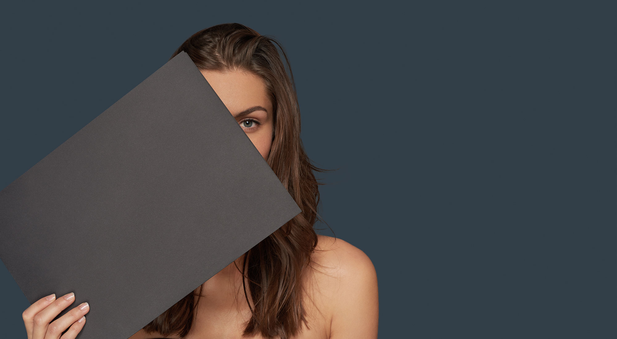 amiea model holding a grey piece of paper on a dark grey background